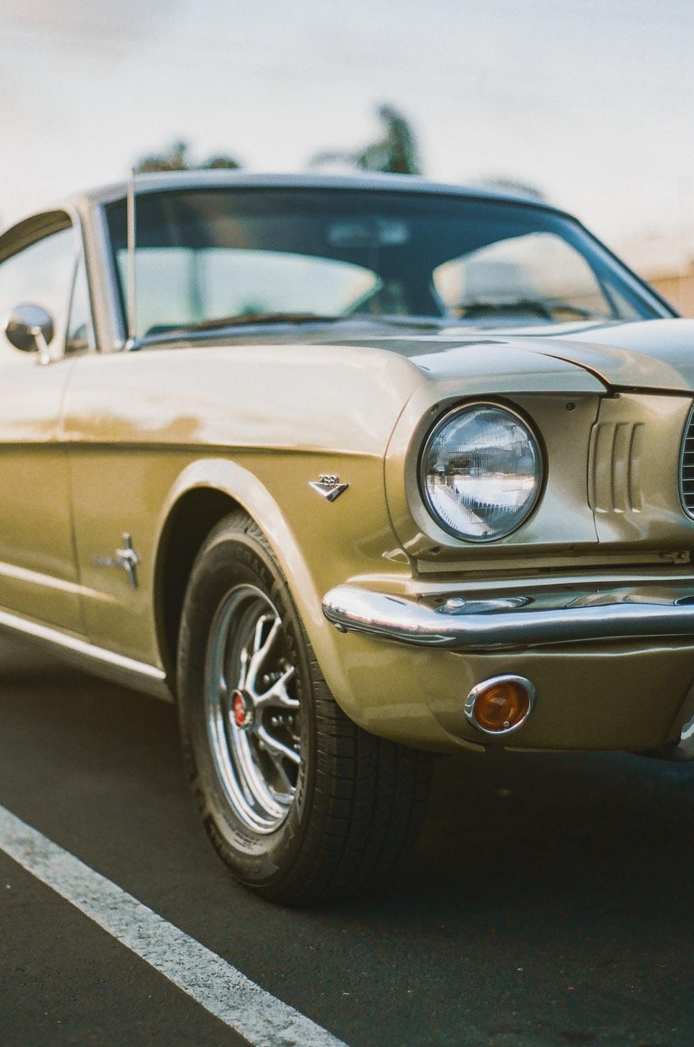 beige vintage car on road