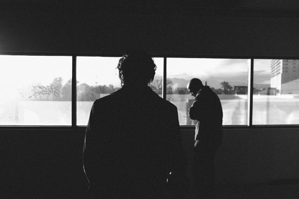 silhouette of man near the glass window