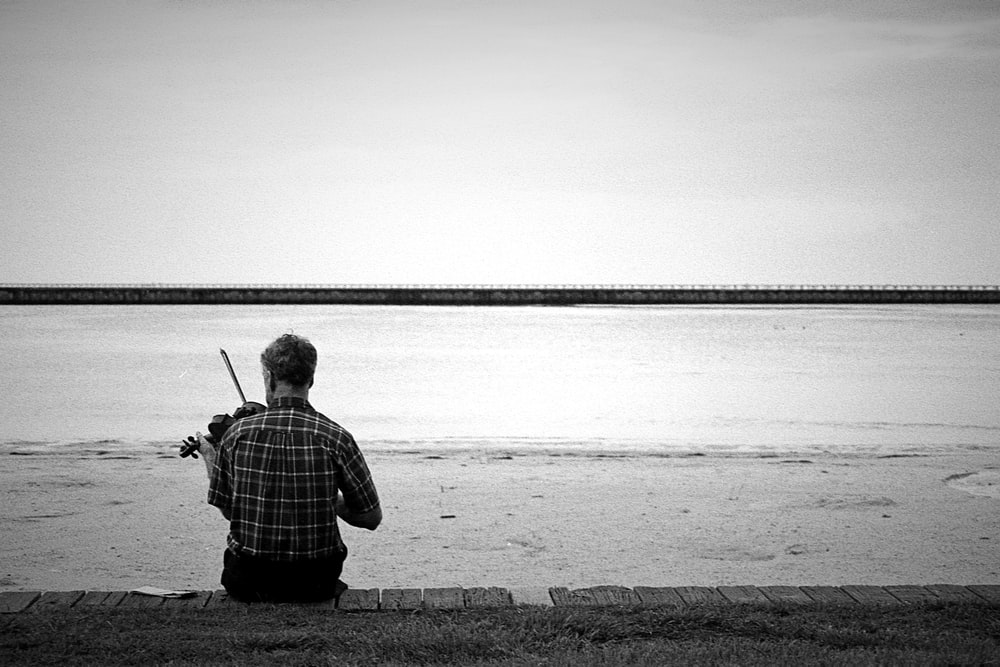 man playing violin on beach
