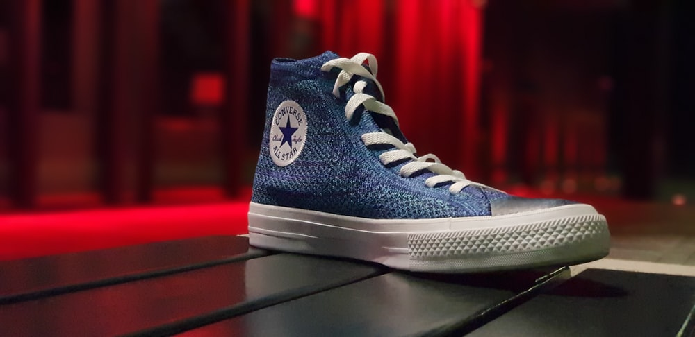 unpaired blue Converse shoe on black surface