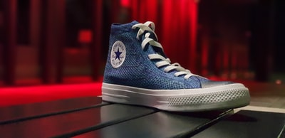 unpaired blue converse shoe on black surface sneaker teams background