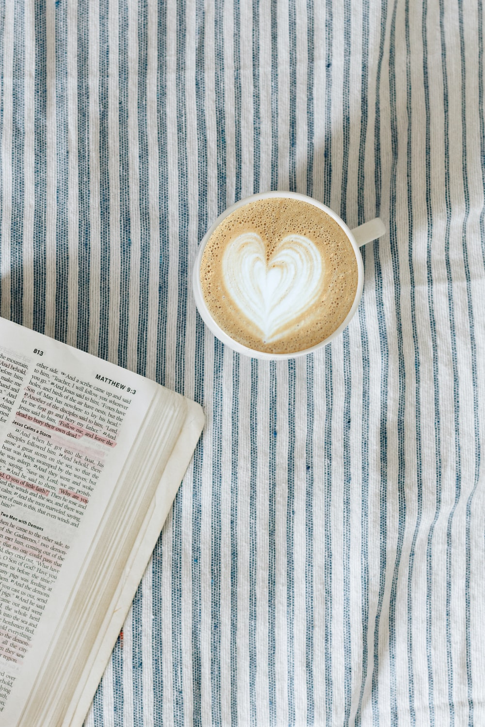 white teacup beside book