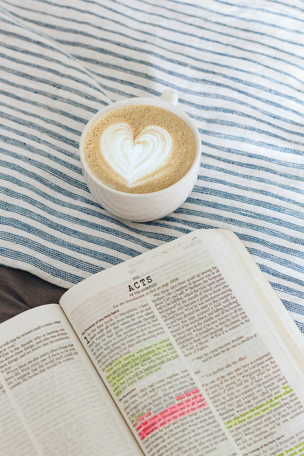cup of brown coffee beside white book