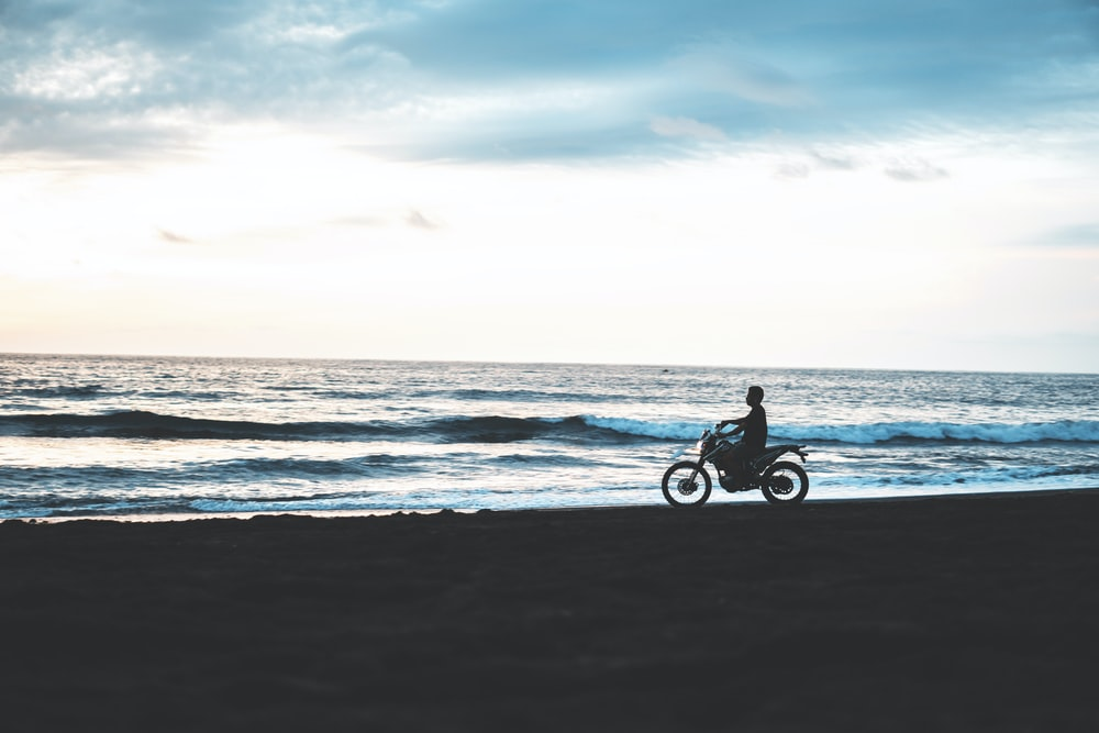 silhouette of man riding motorcycle beside seashore