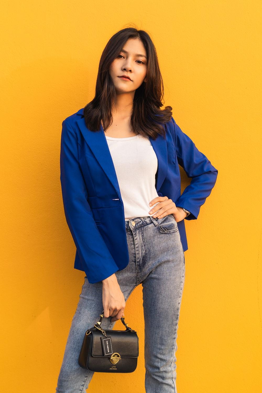 woman in blue suit jacket standing beside wall