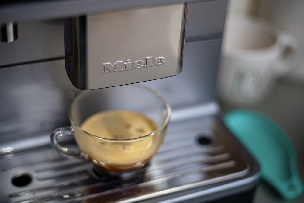 clear glass mug on gray espresso machine