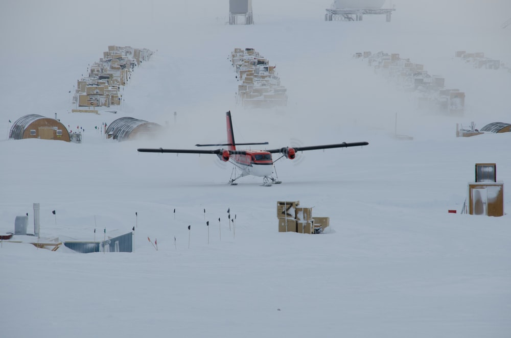 white and brown biplane on snow-covered field