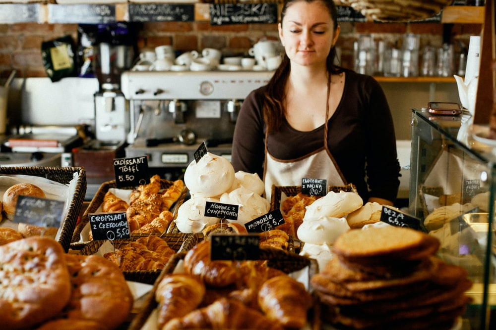 woman on counter near breads