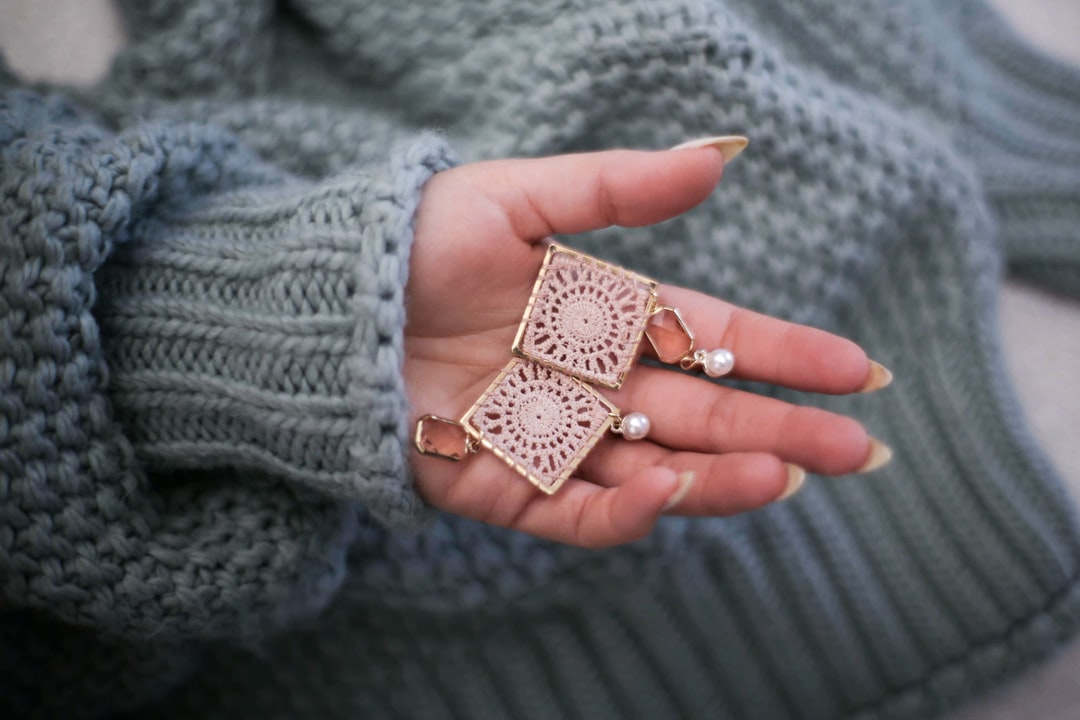 A pair of powder-pink, openwork earrings with pearls on a woman's hand against the background of a thick, gray-green sweater