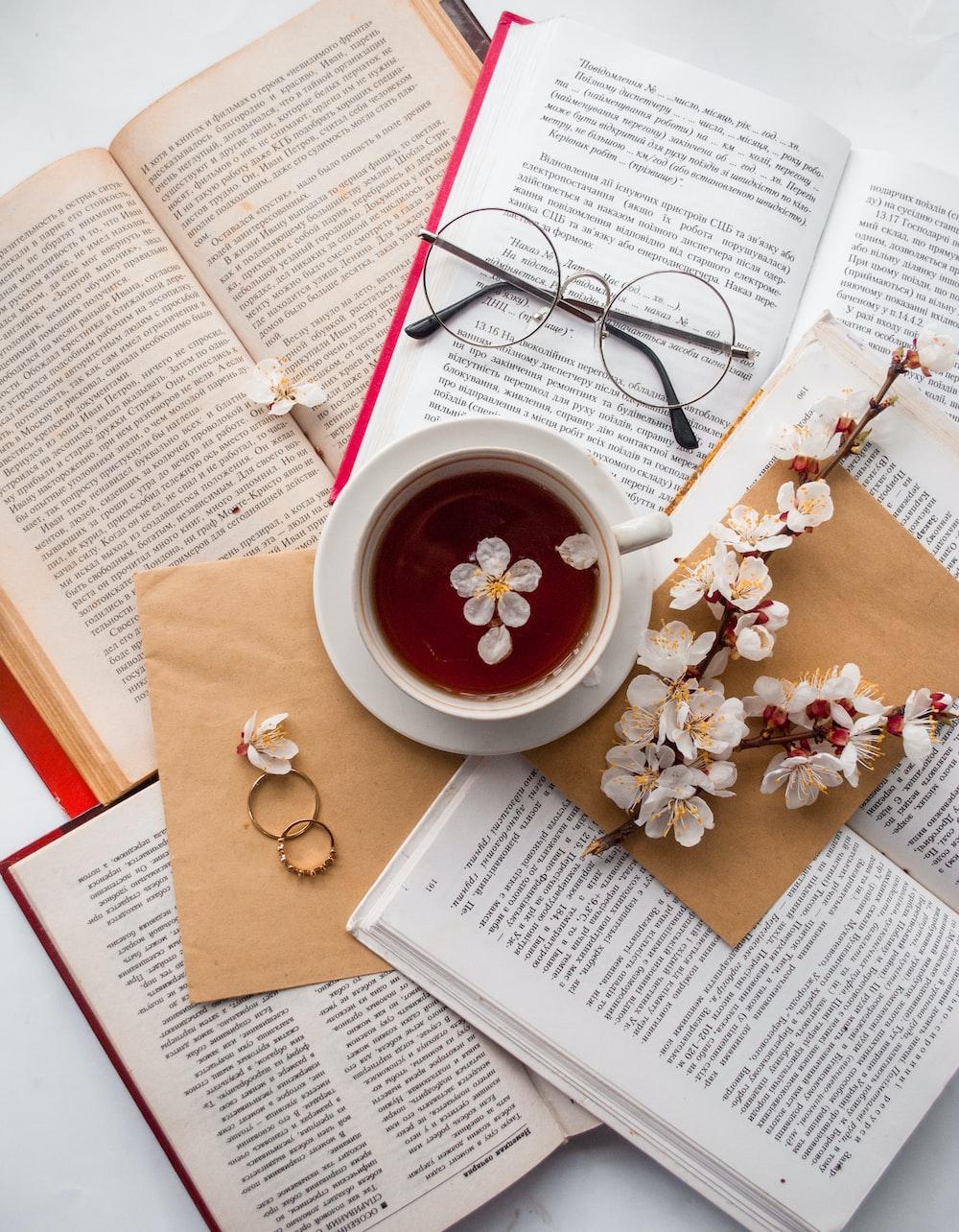 filled teacup on books