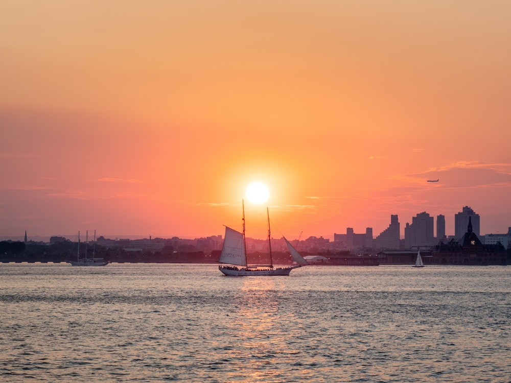 white and brown sailing boat on body of water during golden hour