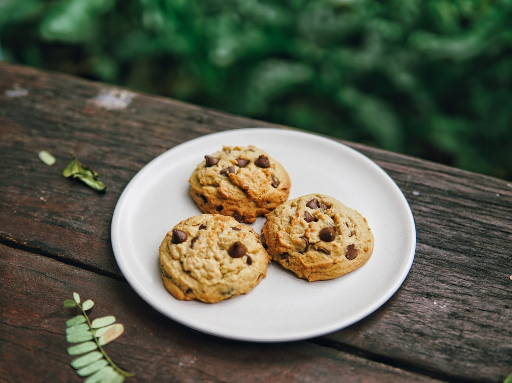 three baked chocolate cookies on white plate