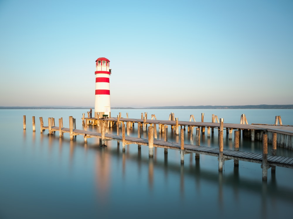 white and red lighthouse on brown wooden dock during daytime