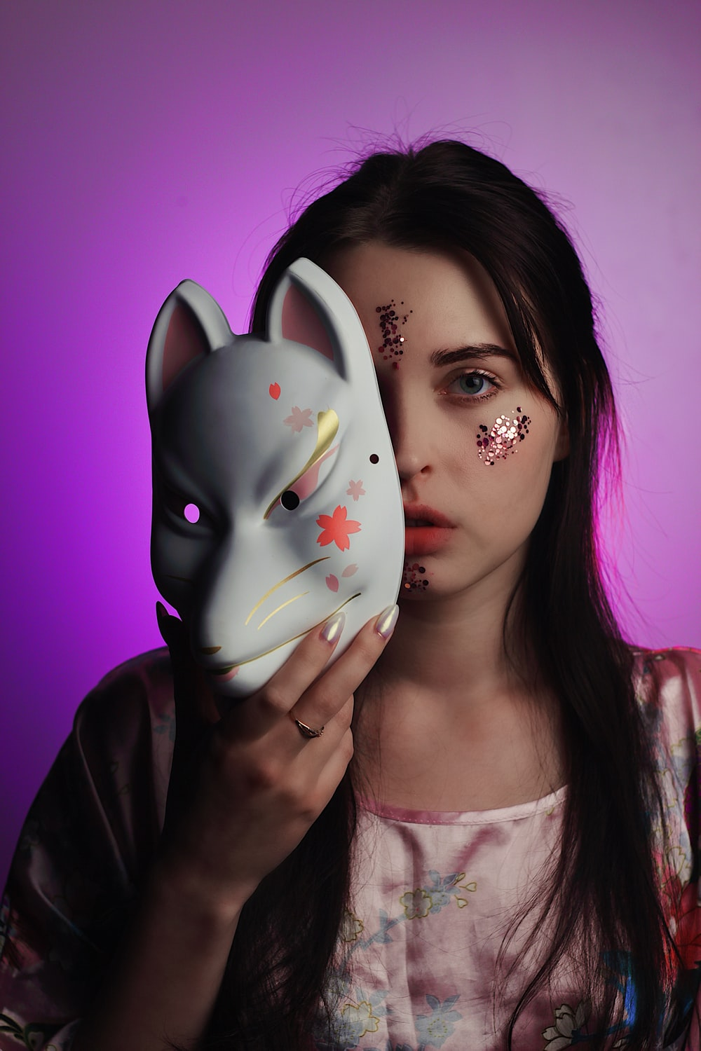 woman holding white and pink cat face mask standing in front of purple background