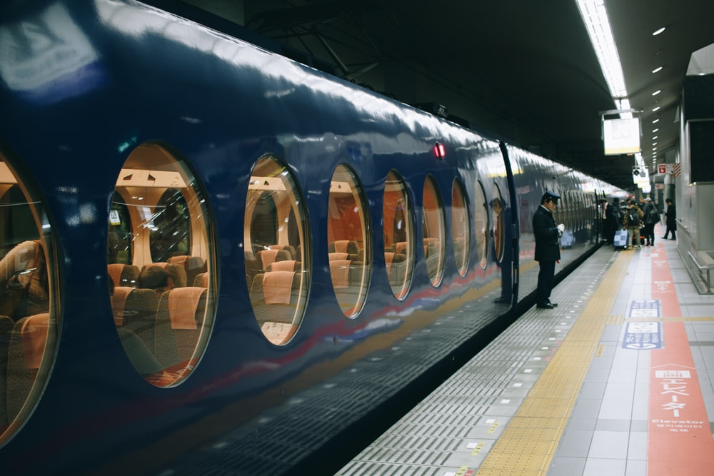 man standing in front of blue and brown train