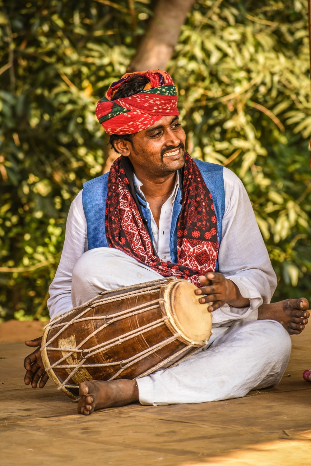 man sitting while holding brown drum