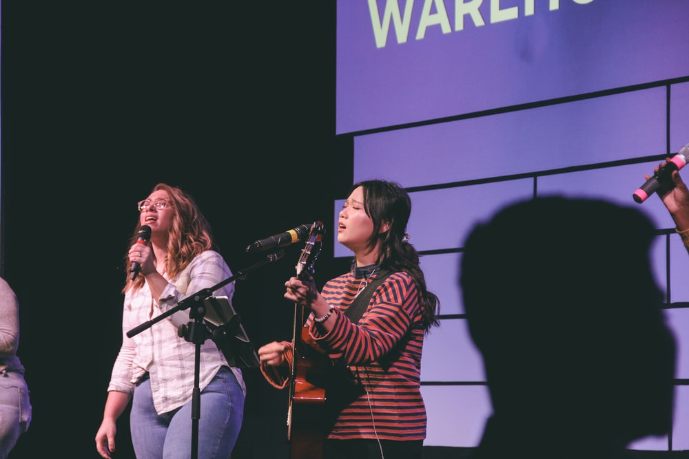 photography of two singing women