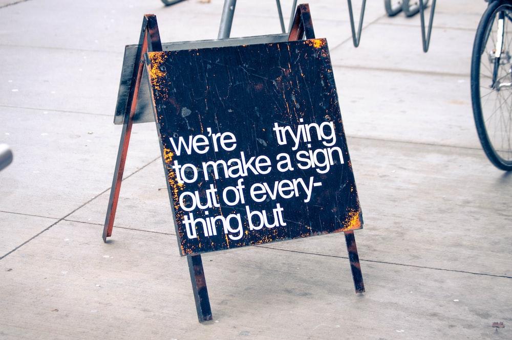 black folding signage on sidewalk