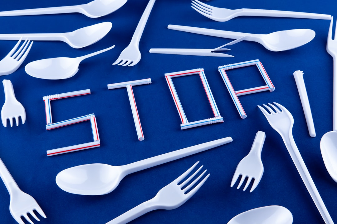 The word stop made of plastic tubes on a blue background with plastic utensils environmental pollution concept. Top view