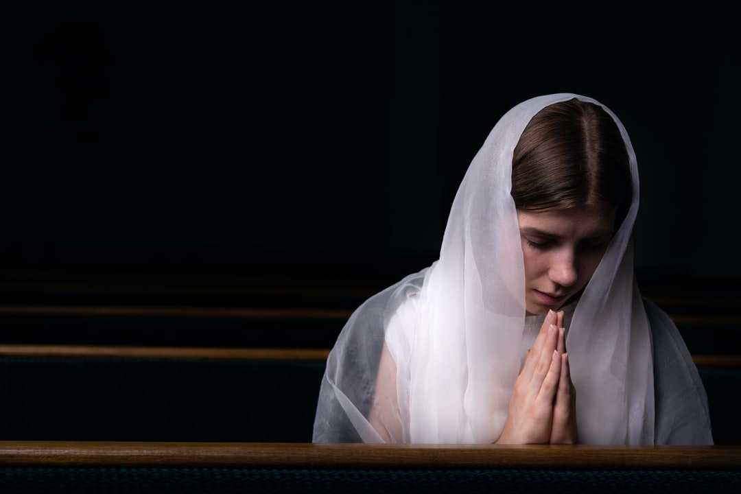 A Young Modest Girl With A Handkerchief On Her Head Is Sitting In Church and Praying. the Concept of Religion, Prayer, Worship. - unsplash