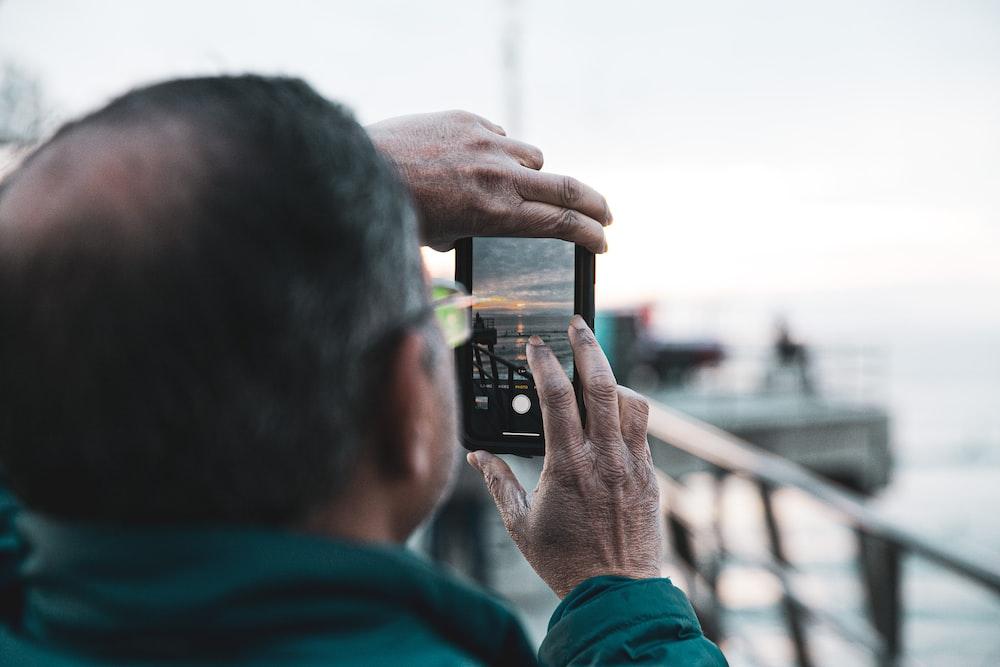 person taking photo of sea