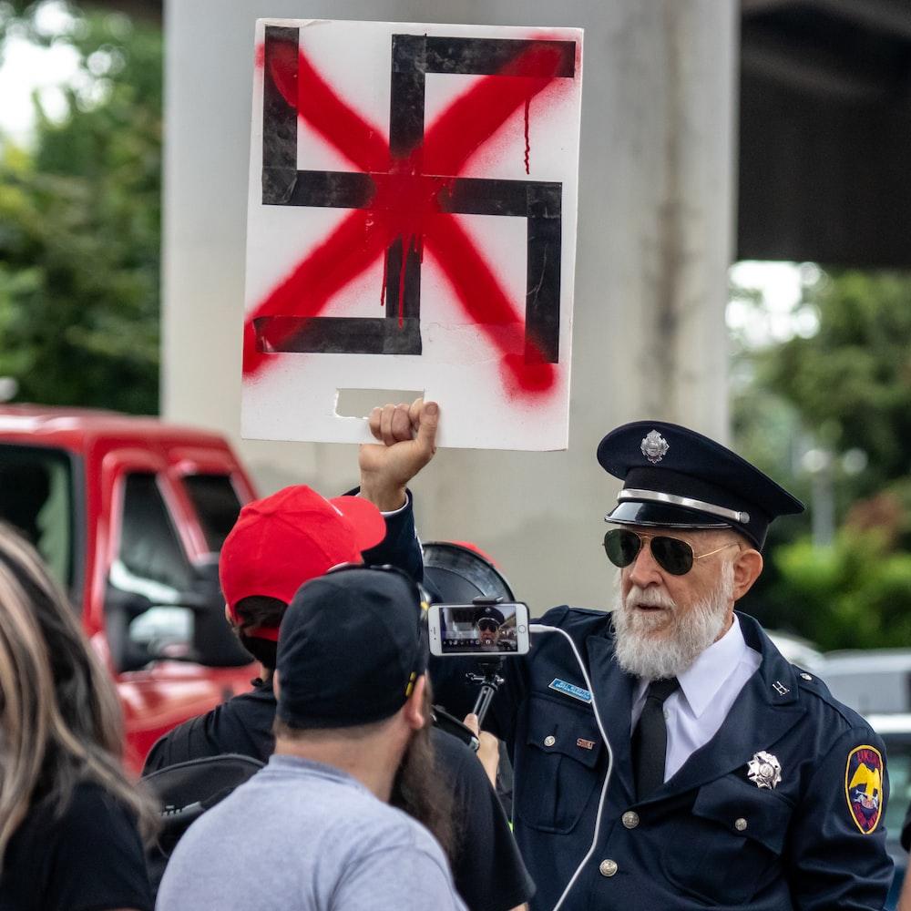man holding swastika logo