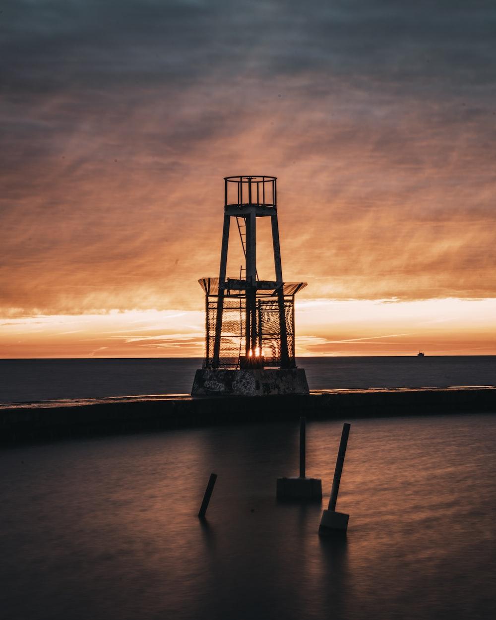 metal tower beside sea during sunset