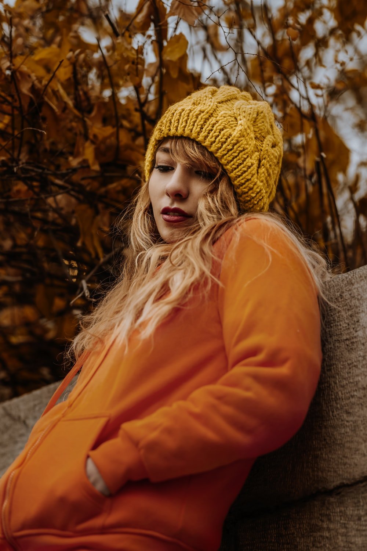 woman in orange jacket sitting on brown wooden bench