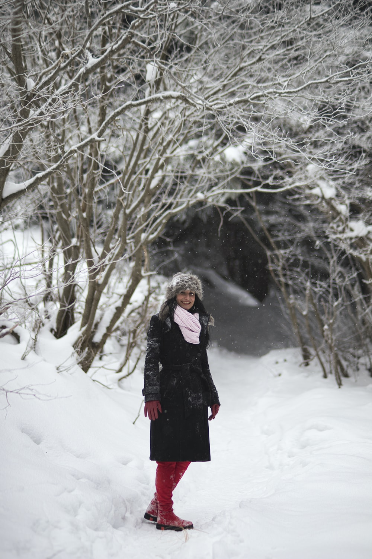 woman in black overcoat in snow