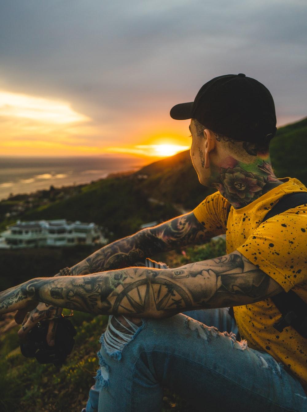 man sitting on hill near cruise ship