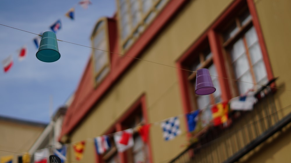 blue and purple disposable cups hanged on cable near houses