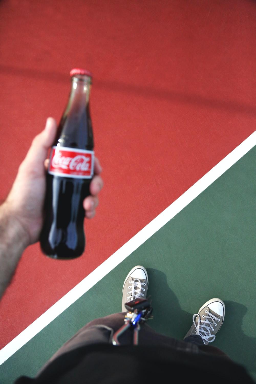 person holding Coca-Cola bottle