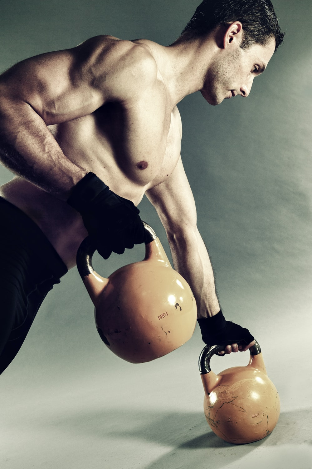 man holding pair of yellow-and-black kettlebells