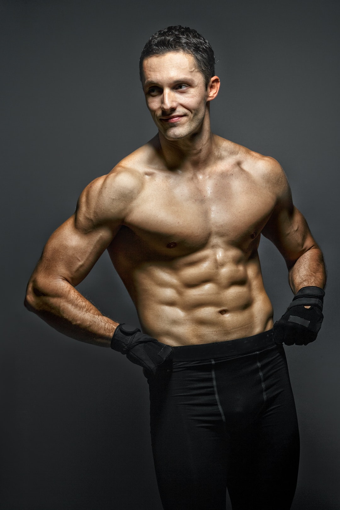 A handsome shirtless man with ripped abs smiling.