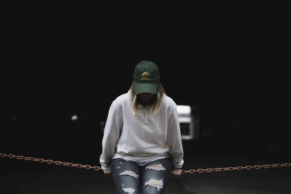 woman in white hoodie leaning on metal chain