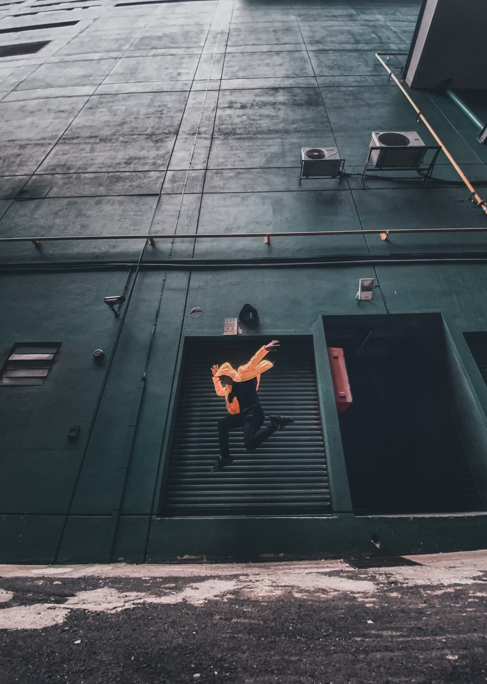 timelapse photography of person jumping near building
