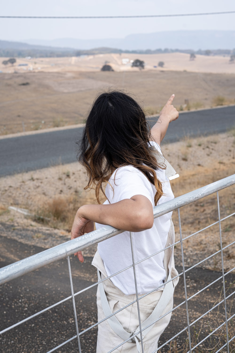 woman points her finger to the east side of the road