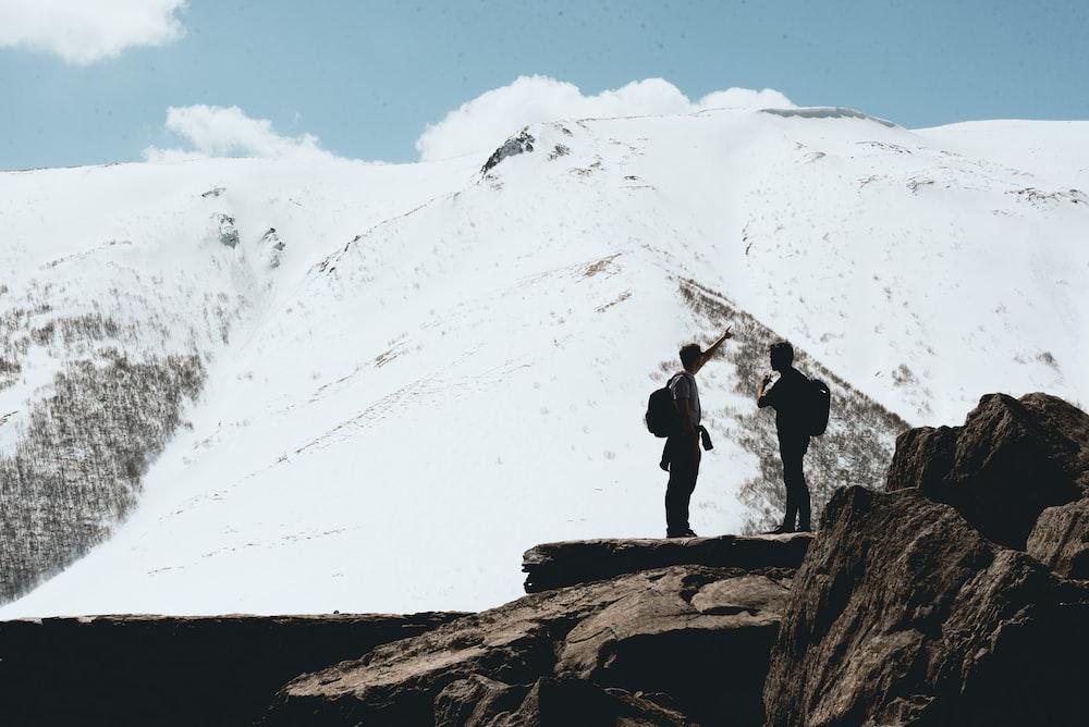 two person standing on stone near mountain range