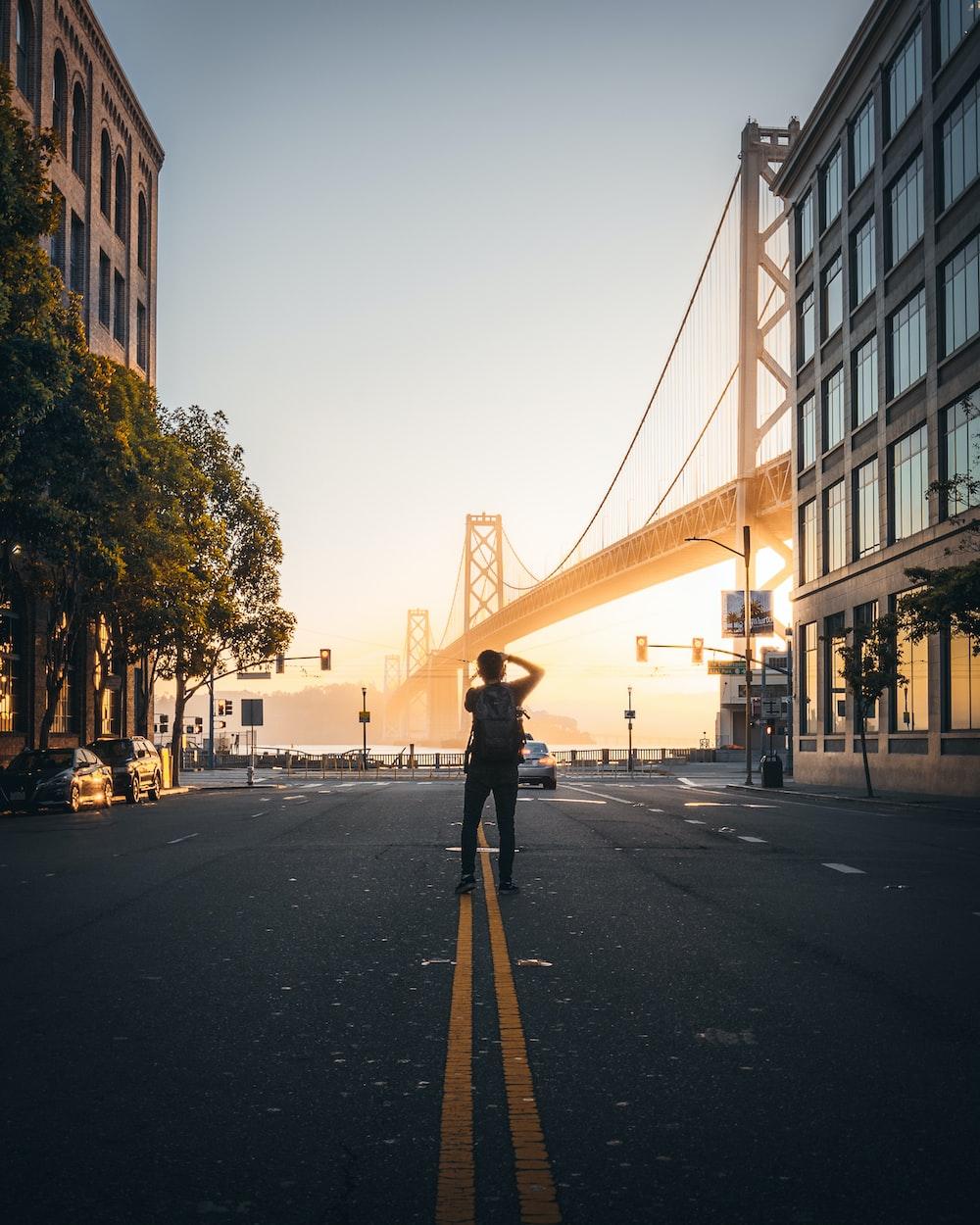 man takes photo of suspension bridge at the city during daytime