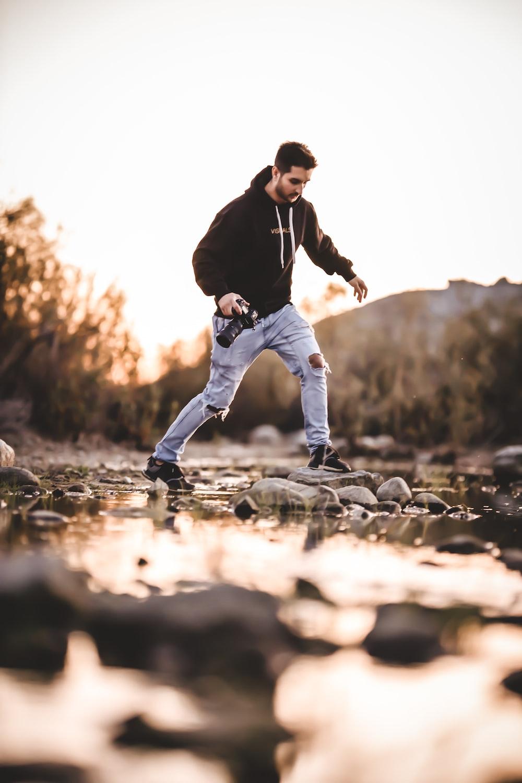 man walking on rocks in river