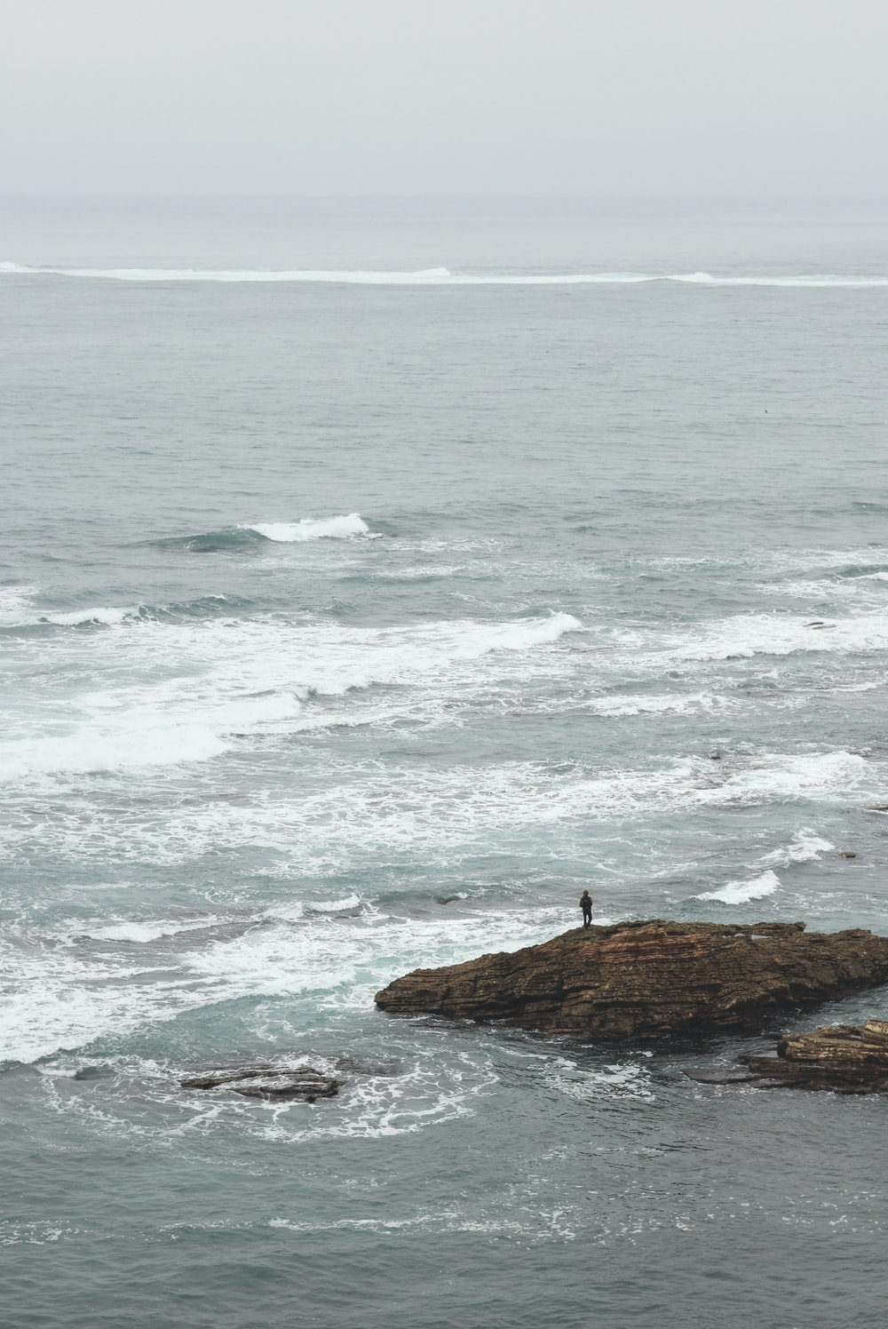 person standing on rock formation near seashore