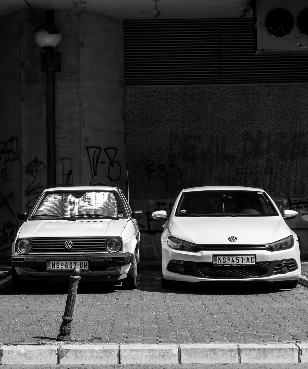 grayscale photo of two Volkswagen cars parked on sidewalk
