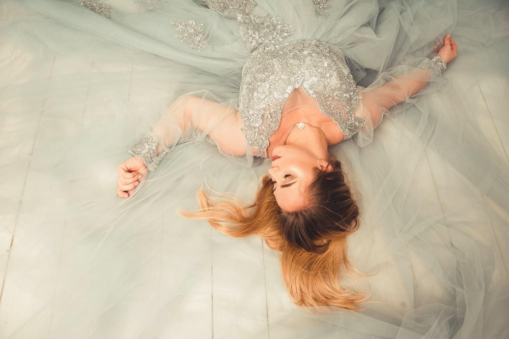 woman in gray V-neck dress lying down