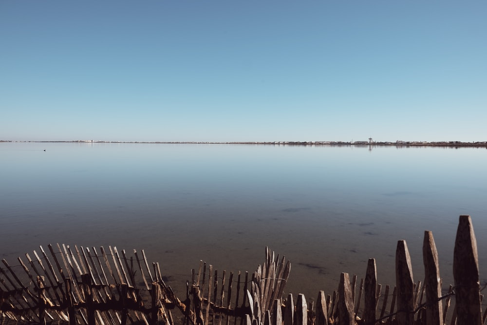 brown wooden fence near blue body of water during daytime