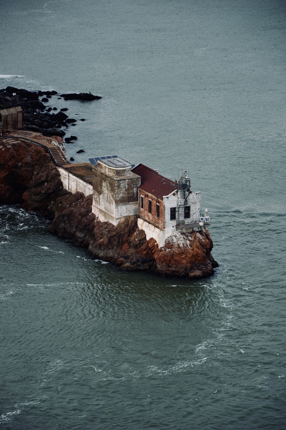 bird's eye photography of white and red concrete house on cliff near body of water