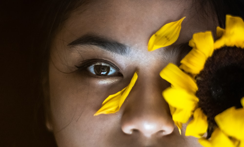 yellow sunflower on person's face