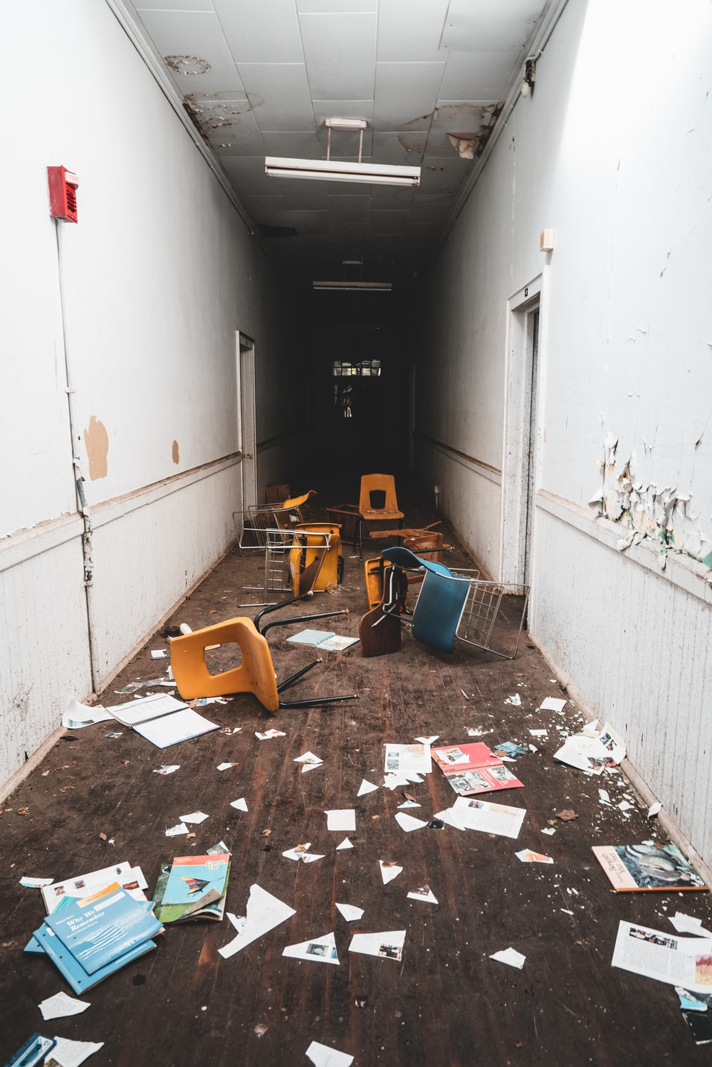 hallway with chairs and papers on floor