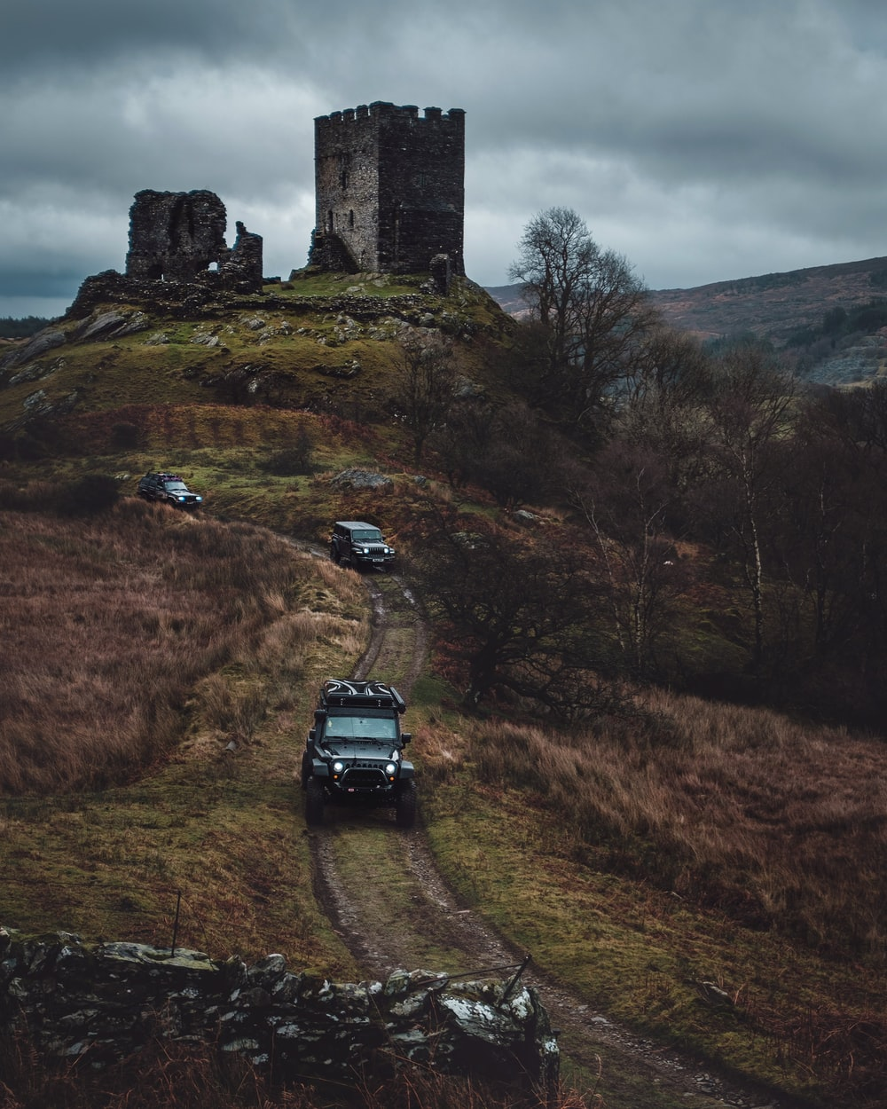 vehicles on road viewing brown ruin castle under white and gray sky