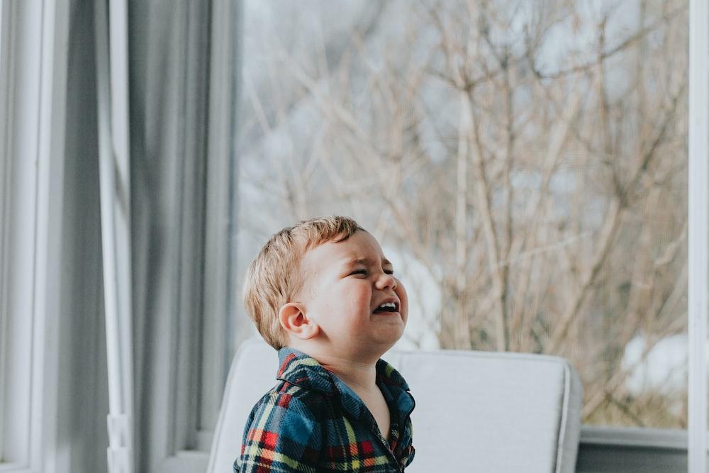 ガラスの壁の近くに座っている少年
