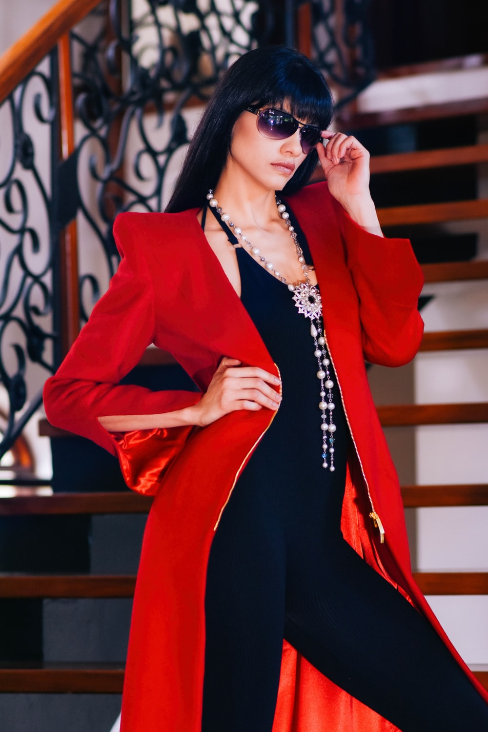 woman wearing red coat and sunglasses standing with right arm akimbo